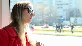 Young blond woman sitting in tram, day dreaming