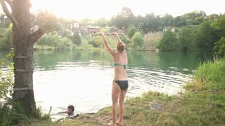 Young blonde girl jumping off rope swing into river at sunset, graded