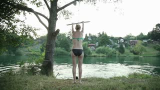 Young blonde girl jumping off rope swing into river at sunset