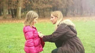 Young blonde mother putting cap on daughter's head and kissing her in forehead in park, graded