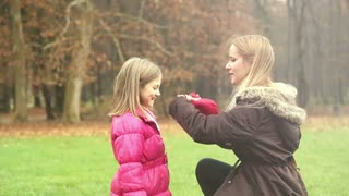 Young blonde mother putting cap on daughter's head and kissing her in forehead in park, slow motion, graded