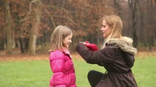 Young blonde mother putting cap on daughter's head and kissing her in forehead in park, slow motion