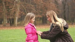 Young blonde mother putting cap on daughter's head and kissing her in forehead in park