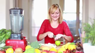 Young blonde woman chopping apple for fruit shake , graded