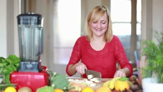 Young blonde woman chopping apple for fruit shake , in slow motion