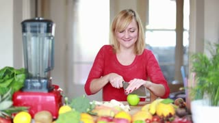 Young blonde woman chopping apple for fruit shake