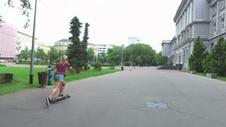 Young blonde woman longboarding with friends in the city park