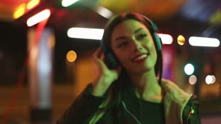 Young brunette woman dancing to the rhythm of music with headphones