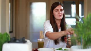 Young brunette woman drinking green smoothie, in slow motion