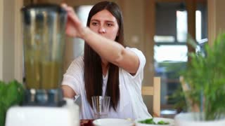Young brunette woman pouring green smoothie into glass