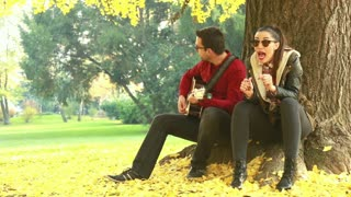 Young brunette woman singing and man playing guitar while sitting on a tree in park, graded