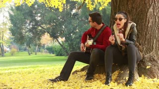 Young brunette woman singing and man playing guitar while sitting on a tree in park
