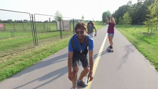 Young cheerful skater having fun riding skate with friends