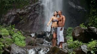 Young couple enjoying waterfall in the tropics