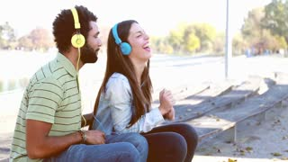 Young couple having fun listening to music on headphones at the park, slow motion, graded