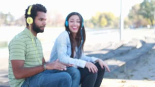 Young couple having fun listening to music on headphones at the park, slow motion