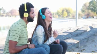 Young couple having fun listening to music on headphones at the park