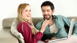 Young couple lounging on couch with laptop at home
