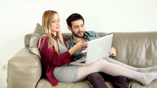 Young couple sitting and talking on couch looking at laptop at home