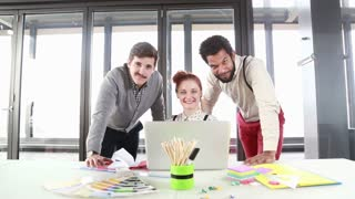 Young creative team smiling and looking at camera in office