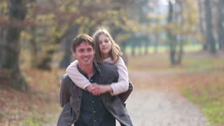 Young dad gives daughter piggyback ride in park