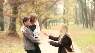 Young family walking in the park, father carrying daughter in his arms and mom tickles her, graded