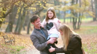 Young family walking in the park, father carrying daughter in his arms and mom tickles her,  slow motion, graded