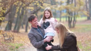 Young family walking in the park, father carrying daughter in his arms and mom tickles her, slow motion