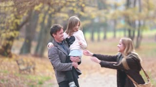 Young family walking in the park, father carrying daughter in his arms and mom tickles her