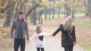 Young family walking in the park, father takes daughter in his arms