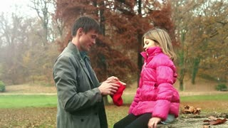 Young father putting red cap on daughter's head in the park, graded