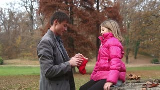 Young father putting red cap on daughter's head in the park