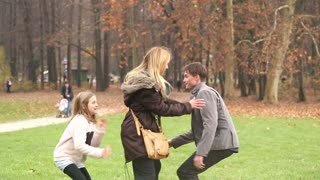 Young father trying to catch daughter while she's hiding behind mother in park