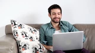 Young handsome adult man sitting on couch in living room and having video chat
