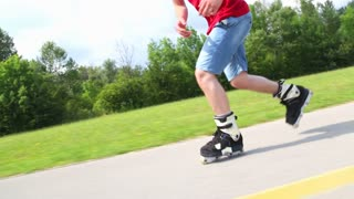 Young handsome man rollerblading in park on a beautiful day, doing some tricks