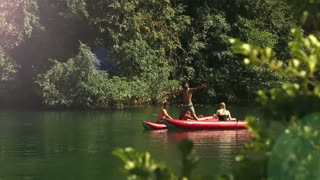 Young handsome man standing on a canoe and having fun with his friends on the Mreznica river, graded, in slow motion