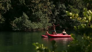Young handsome man standing on a canoe and having fun with his friends on the Mreznica river, in slow motion