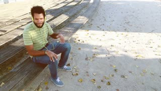 Young handsome man with headphones listening to music and singing while sitting on park bench, graded