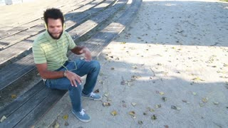Young handsome man with headphones listening to music and singing while sitting on park bench