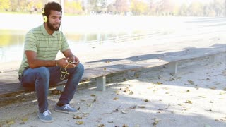 Young handsome man with headphones listening to music on smartphone while sitting on park bench, graded