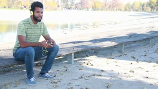 Young handsome man with headphones listening to music on smartphone while sitting on park bench