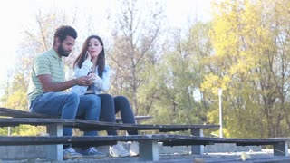 Young happy couple sharing earphones while listening to music on smartphone at park