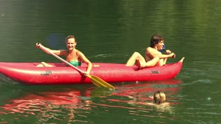 Young happy friends splashing girl in water with paddles on beautiful Mreznica river, graded