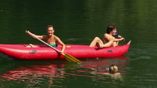Young happy friends splashing girl in water with paddles on beautiful Mreznica river