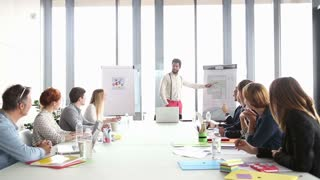 Young male advertising executive pointing at flipchart during presentation in conference room