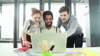 Young male creative executive high-fiving with colleagues in office