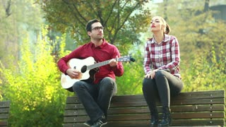 Young man and beautiful woman sitting on park bench, playing guitar and having fun