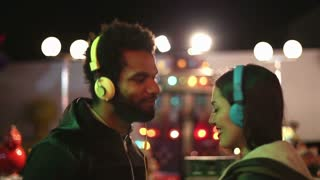 Young man and woman dancing to the rhythm of music with headphones in amusement park, sending kiss and wink to camera
