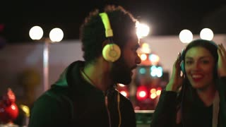 Young man and woman dancing to the rhythm of music with headphones in amusement park