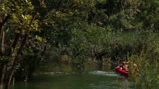 Young man and woman enjoying riding canoe on the Mreznica river